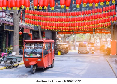 Red retro motorbike on the ancient street of Xian city decorated with traditional red lanterns in honor of the Chinese New Year holiday
