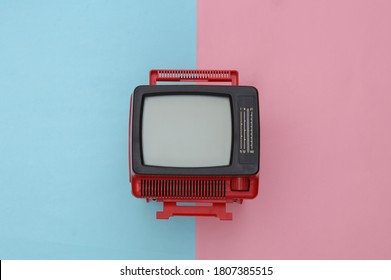 Red retro old mini tv set on pink blue pastel background. Top view
