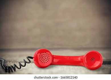 Red retro telephone handset on the desk
