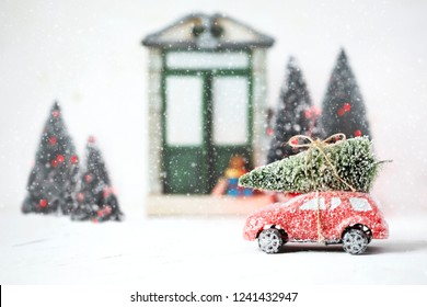 Red retro toy car delivering Christmas Tree. Holiday card