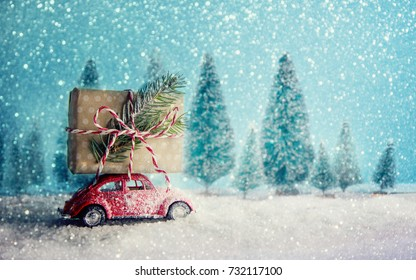 Red retro toy car delivering Christmas or New Year gifts on festive background