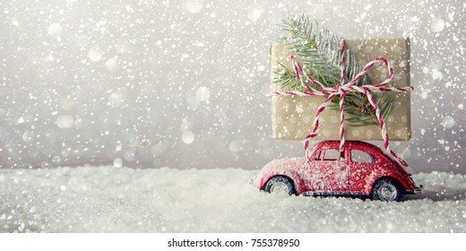 Red retro toy car delivering Christmas or New Year gifts on festive background.