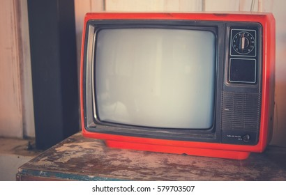 The red retro TV on the wooden table