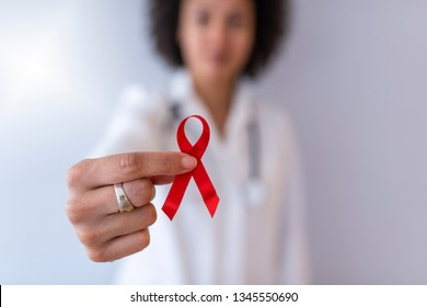 Red ribbon for cancer awareness. Support people living with tumor illness. Doctor Hands Holding Red Cancer Awareness Ribbon. Concept of medicine oncology closeup