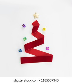 RED RIBBON CHRISTMAS TREE ON WHITE BACKGROUND, MINIMAL CHRISTMAS BACKGROUND, TOP VIEW