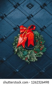 Red ribbon christmas wreath hanging on riveted wrought iron door