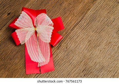 red ribbon gift bow on wooden board background,satin bow