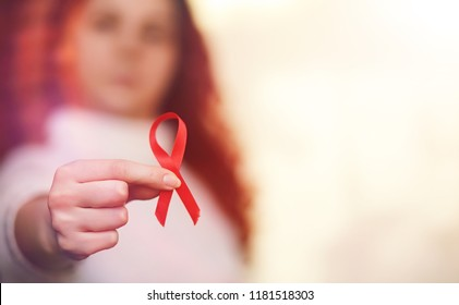 The red ribbon of the girl. The girl is holding a red ribbon. Health concept red ribbon. Breast cancer.