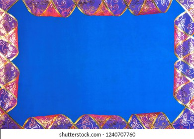 A red ribbon with a gold pattern frame on a blue background, decoration, festive event. Tape ideal attribute is widely used in the creation of original art paintings, the main attribute in the design