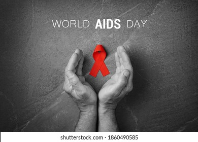 Red ribbon in hands on gray background, World Cancer Day, symbol of fight against HIV, AIDS and cancer. Concept of helping those in need. First december World AIDS Day Cancer Control. Black and white.