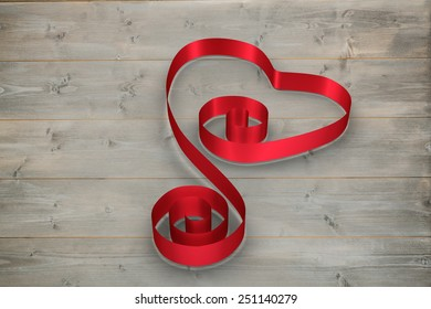 Red ribbon heart against bleached wooden planks background