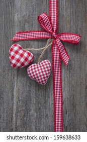 Red ribbon with hearts on a wooden background