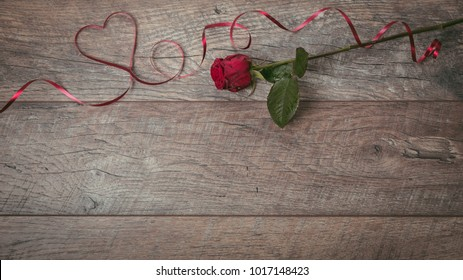 The red ribbon is lined in the shape heart on a dark wooden table. Valentines day background, rustic style. Valentines day table place setting with red rose and ribbon. Flat lay, top view