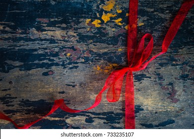 Red ribbon on dark vintage wooden background as a Christmas concept