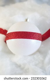 Red ribbon over white Christmas ornament
