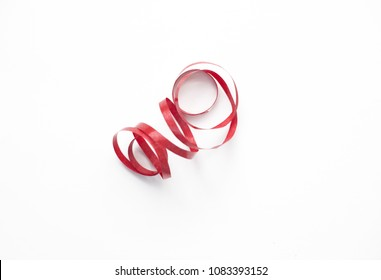 Red ribbon serpentine on white background isolate