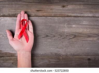 Red ribbon as symbol of aids awareness in men's hand