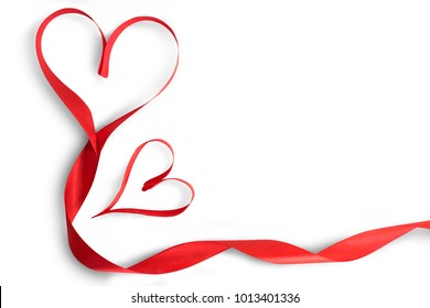 Red ribbon tied like a two hearts being together and leaved its tail in swirled shape. Valentine decoration. Isolated on white background, dicut with clipping path.