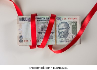 Red ribbon wrapped around a bundle of hundred Indian rupee currency notes. Indian bank notes on white background.
