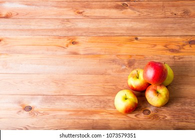 red rich apples on a wooden table