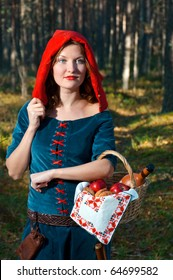 red Riding  hood standing in a wood . beautiful girl in medieval dress