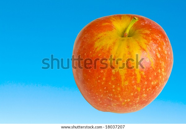 Red ripe apple on clear blue sky. Clipping path.