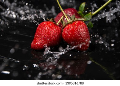 """Red, ripe berry, strawberries """"Fragaria ananassa""""  on a black wooden table. Water splash, slow motion. Close-up photo."""