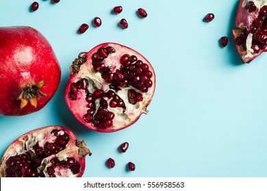 Red ripe pomegranates on blue background, copy space, top view.