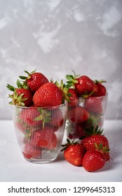 Red ripe strawberry in glass bowls on gray concrete table background, copy space. Healthy food concept