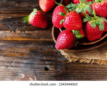 red ripe strawberry in a wooden bowl on a rustic table, close-up, selective focus