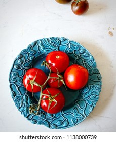 red ripe summer tomatoes on a blue ceramic plate in the kitchen