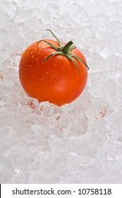 A red ripe tomato kept fresh on a bed of ice.
