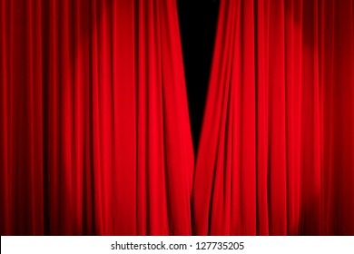 Red rising curtain with a light spot in a theater