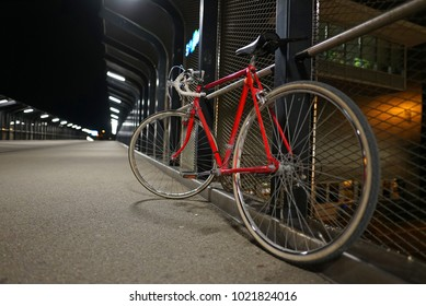 Red road bike by fence