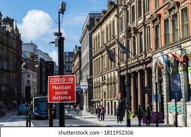 A red road sign reminding people to maintain social distance seen in Liverpool, England in September 2020 during the Covid19 pandemic.