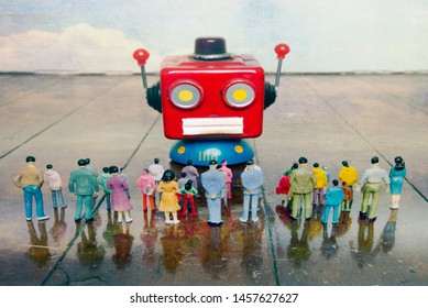red robot head talks to a crowed of plastic people on a old wooden floor