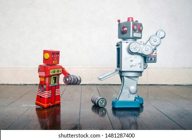 red robot helping big silver robot with a power problem