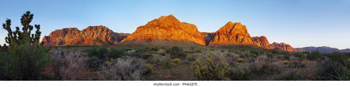 Red Rock Canyon cliffs and desert lit up by the sunrise light