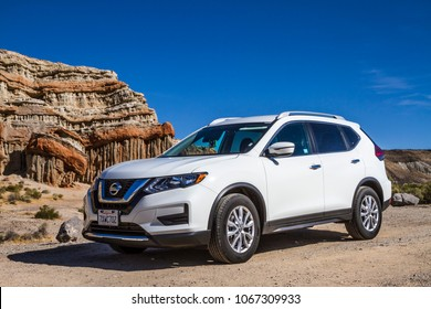 Red Rock Canyon State Park, California / USA - 05 16 2017: White Nissan Rogue on gravel road in front of sandstone formation in desert wilderness area