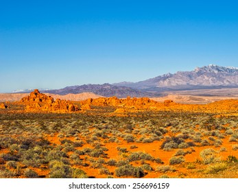 Red rock formations in Valley of Fire State Park, Nevada, USA, with snow-covered mountains in the background, clear blue sky and copy space.. Valley of Fire is in the Mojave Desert in southern Nevada.