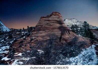 A red rock layered hill in a snow covered terrain at dusk in Zion National Park, near Springdale, Utah, USA.