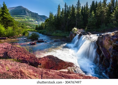 Red rocks and cascading water falls in east Glacier National Park, Montana