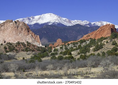 Red rocks at Garden of the Gods in Colorado Springs with Pikes Peak in background.