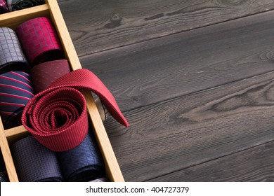 red rolled necktie on top of collection of coiled neckties on display, copy space