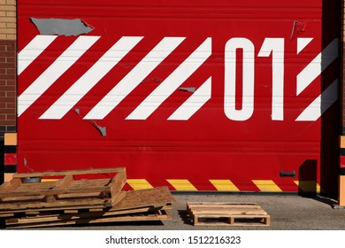 Red roller door with chevron pattern and the number two and foreground pallets