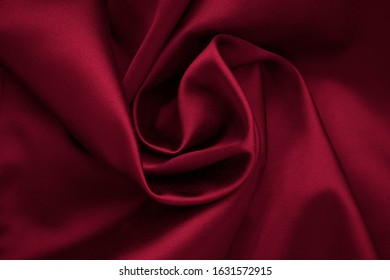 Red romantic fabric background. Folds of silk, dark satin, creases textile, natural pattern, shiny texture of cloth.