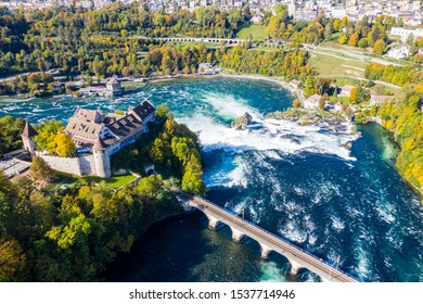 Red roofs and towers of cliff-top Schloss Laufen castle, Laufen-Uhwiesen. Rhine Falls or Rheinfall, Switzerland. Rail road bridge between cantons Schaffhausen and Zürich. Panoramic aerial view