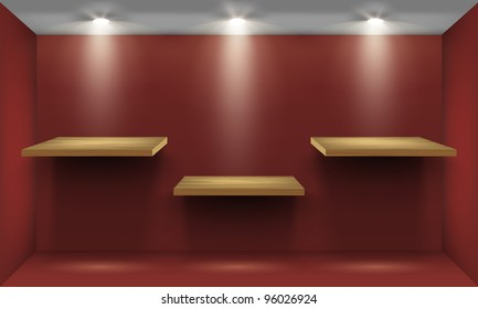 Red room with three empty wooden shelf, illuminated by searchlights.