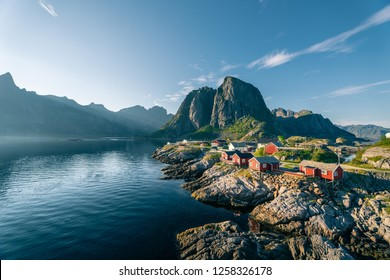Red rorbu huts by an calm ocean at sunny summer evening in Lofoten islands, Reine, Norway