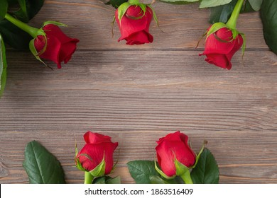 Red rose background for Valentines day, Mothers day, Birthday card. Flowers frame on the brown wooden table flat lay with copy space.